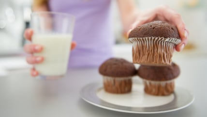 Closeup on teenager girl with milk taking chocolate muffin; Shutterstock ID 139199882; PO: today.com