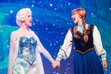 Actors playing Elsa and Anna sing at a Disney show.