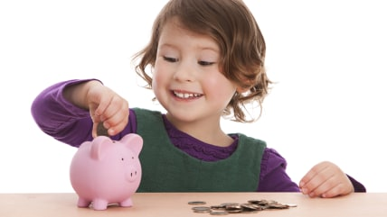 Adorable preschooler putting money into her piggy bank.  Isolated on white.; Shutterstock ID 188215700; PO: kids-allowance-preschool-TODAY-150225; Cli...