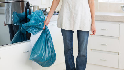 Low section of a young woman carrying garbage bag in the kitchen at house; Shutterstock ID 171647774; PO: TODAY.com
