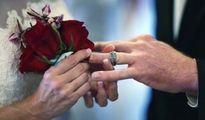 WEST PALM BEACH, FL - FEBRUARY 14:  Luanne Round slips a ring on the finger of her husband Matthew Round as they are wed during a group Valentine's da...