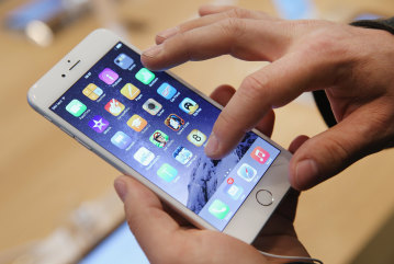 BERLIN, GERMANY - SEPTEMBER 19:  A shopper ltries out the new Apple iPhone 6 at the Apple Store on the first day of sales of the new phone in Germany ...