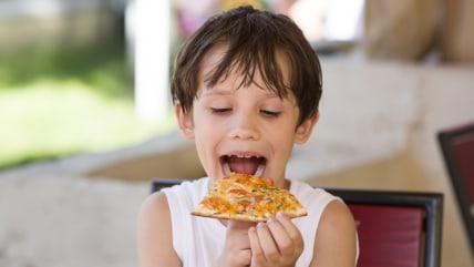 boy eating pizza in a restaurant; adorable; anticipation; anxious; appetite; appetizing; baked; boy; charming; child; cooked; crust; cute; delicious; ...