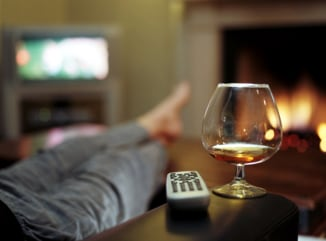 Person in in living room (focus on brandy glass and remote control) couch potato lazy laziness relax relaxed relaxation telelvision drink alcohol fire...