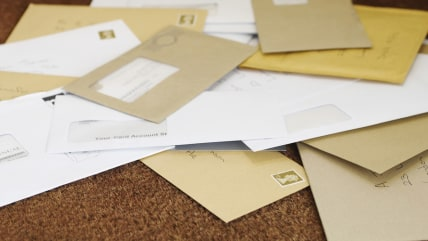Closeup of a pile of mail on doormat; absence; bill; closeup; communication; concern; correspondence; dated; delivery; doormat; envelope; enveloped; f...
