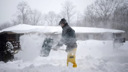 A man shovels snow from his driveway in the Suffolk County city of Dix Hills, New York January 27, 2015. A blizzard swept across the northeastern Unit...