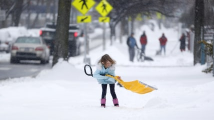 A young girl plays with a shovel following an overnight snowstorm in Jersey City, N.J.