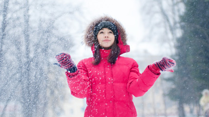 Happy young woman plays with a snow outdoor. Winter day; air; attractive; background; beauty; blow; blue; caucasian; cheerful; christmas; cold; cool; ...
