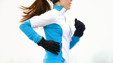 Running athlete woman sprinting during winter training outside in cold snow weather. Close up showing speed