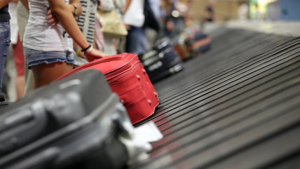 Suitcase on luggage conveyor belt in the baggage claim at airport; Shutterstock ID 153920459; PO: MC for TODAY