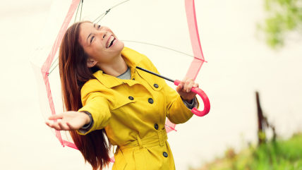 Fall woman happy after rain walking with umbrella. Female model looking up at clearing sky joyful on rainy Autumn day wearing yellow raincoat outside ...