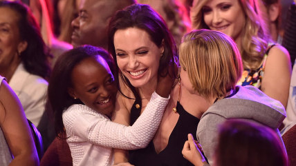 Actress Angelina Jolie hugs Zahara Marley Jolie-Pitt and Shiloh Nouvel Jolie-Pitt after winning award for Favorite Villain in 'Maleficent' during Nick...