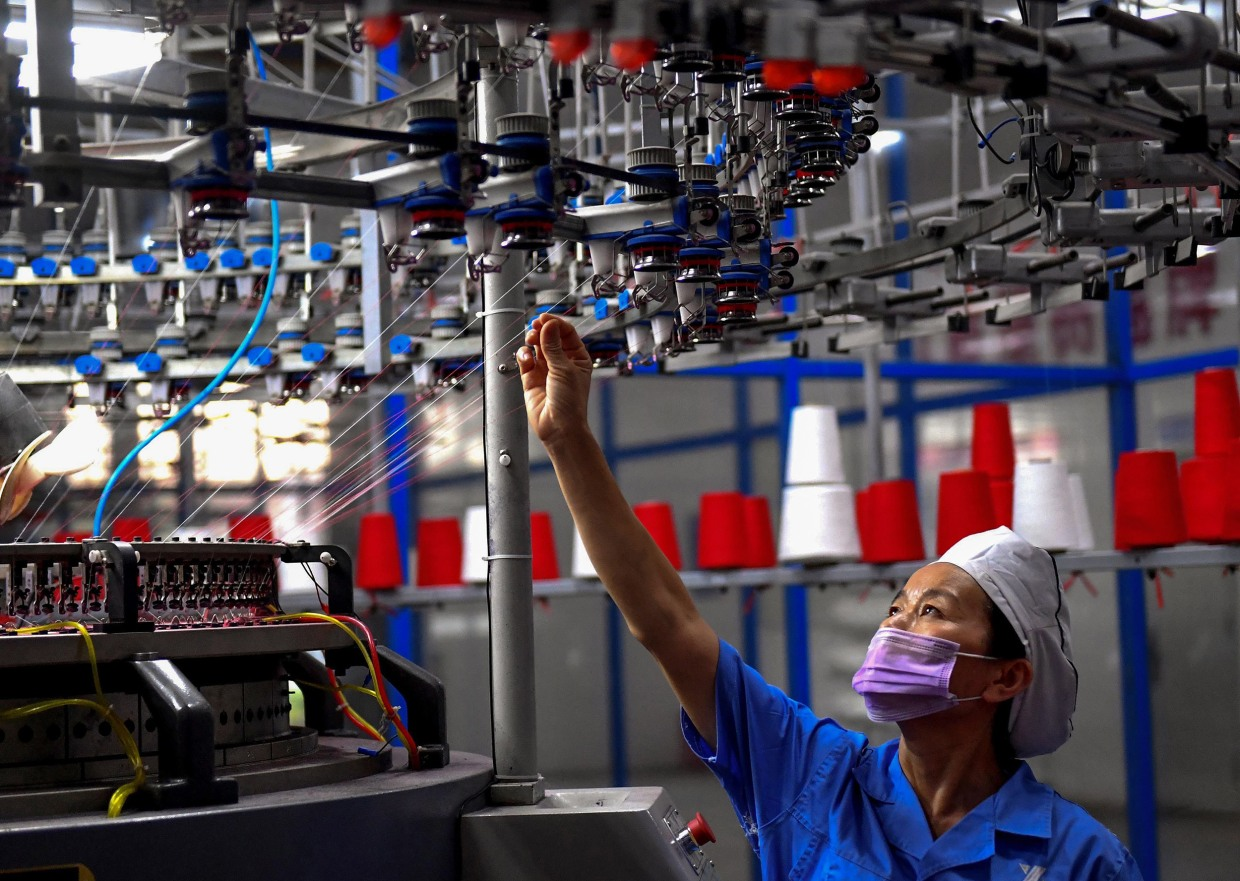 Image: An employee monitors a circular weaving machine at a textile factory in Shangqiu, China