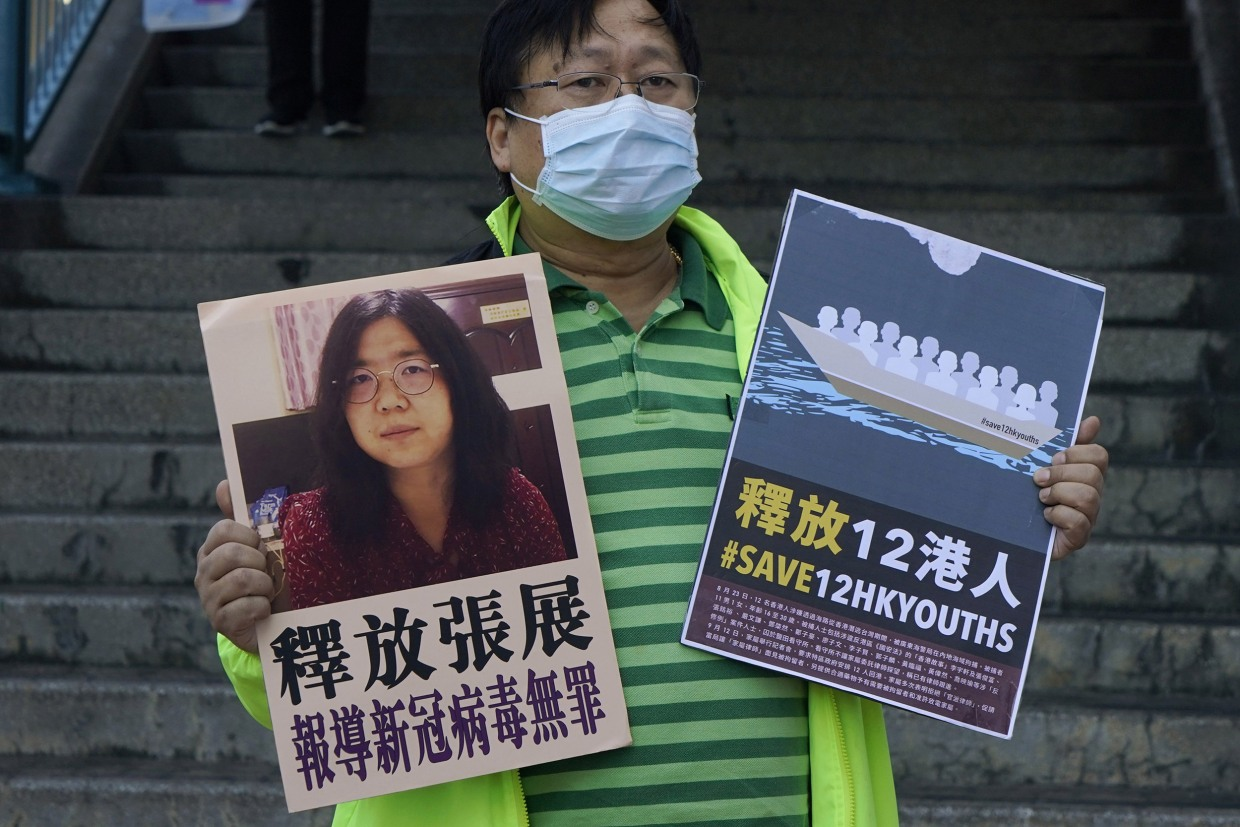 Image: A pro-democracy activist holds placards with the picture of Chinese citizen journalist Zhang Zhan outside the Chinese central government's liaison office, in Hong Kong
