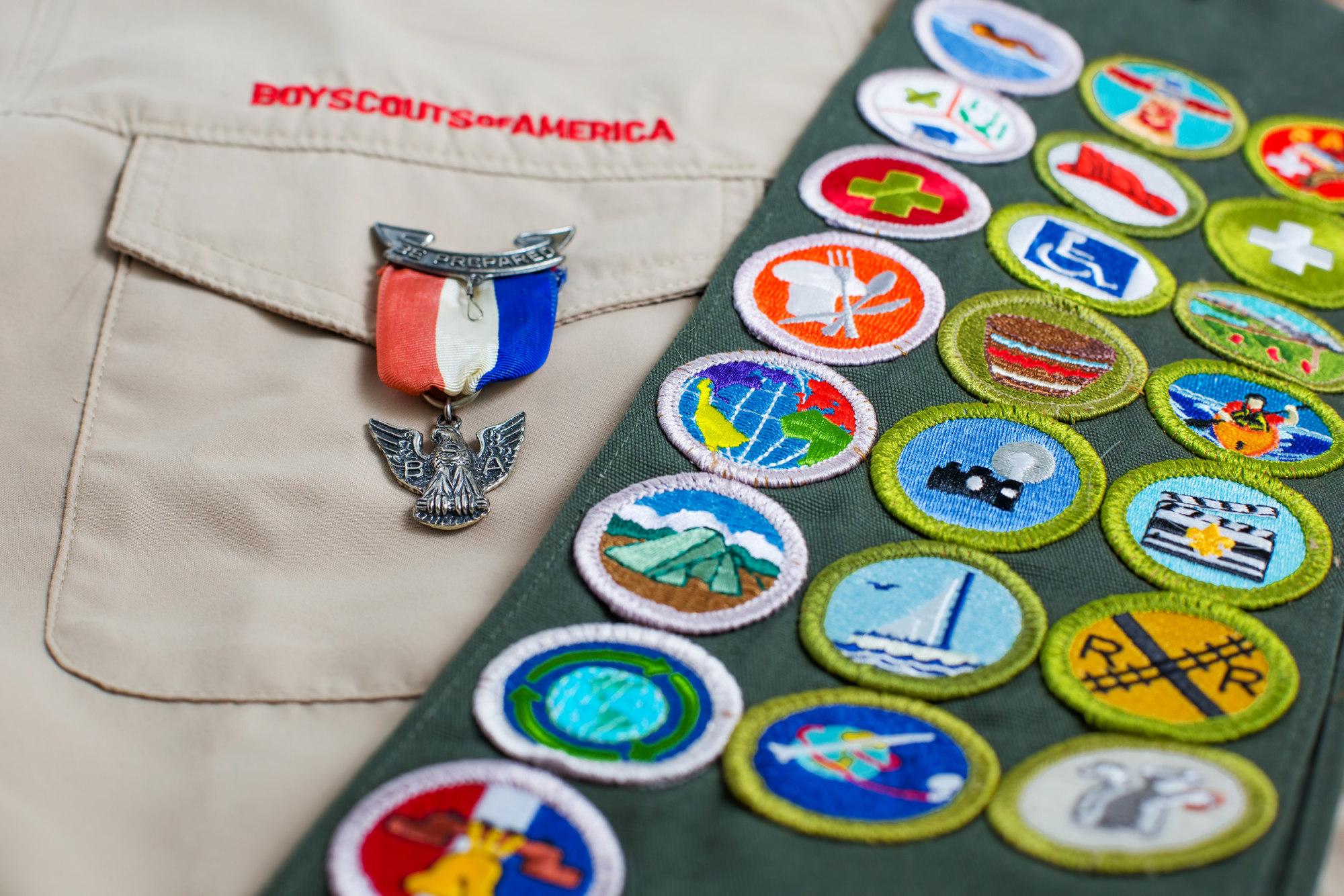 Eagle pin and merit badge sash on boy scout uniform