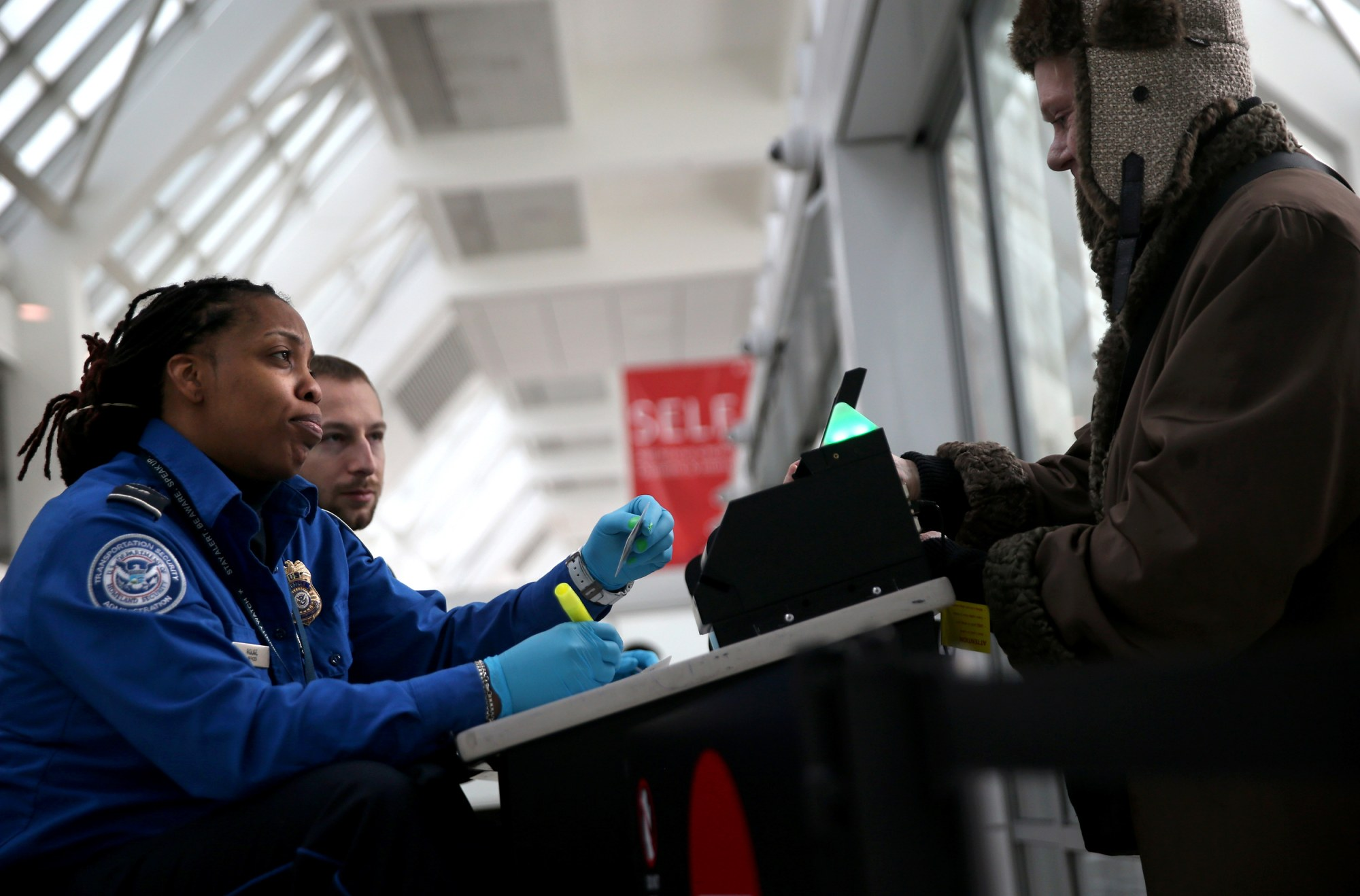 Image: A TSA agent checks a travelers identification at LaGuardia Airport in N.Y. in 2014.