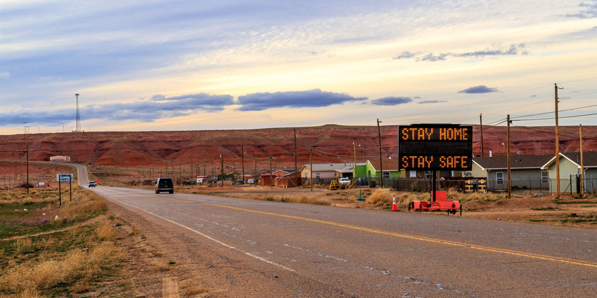 A sign in Many Farms, Ariz., tells Navajos to stay home as the tribal nation experiences an increasing number of coronavirus cases.