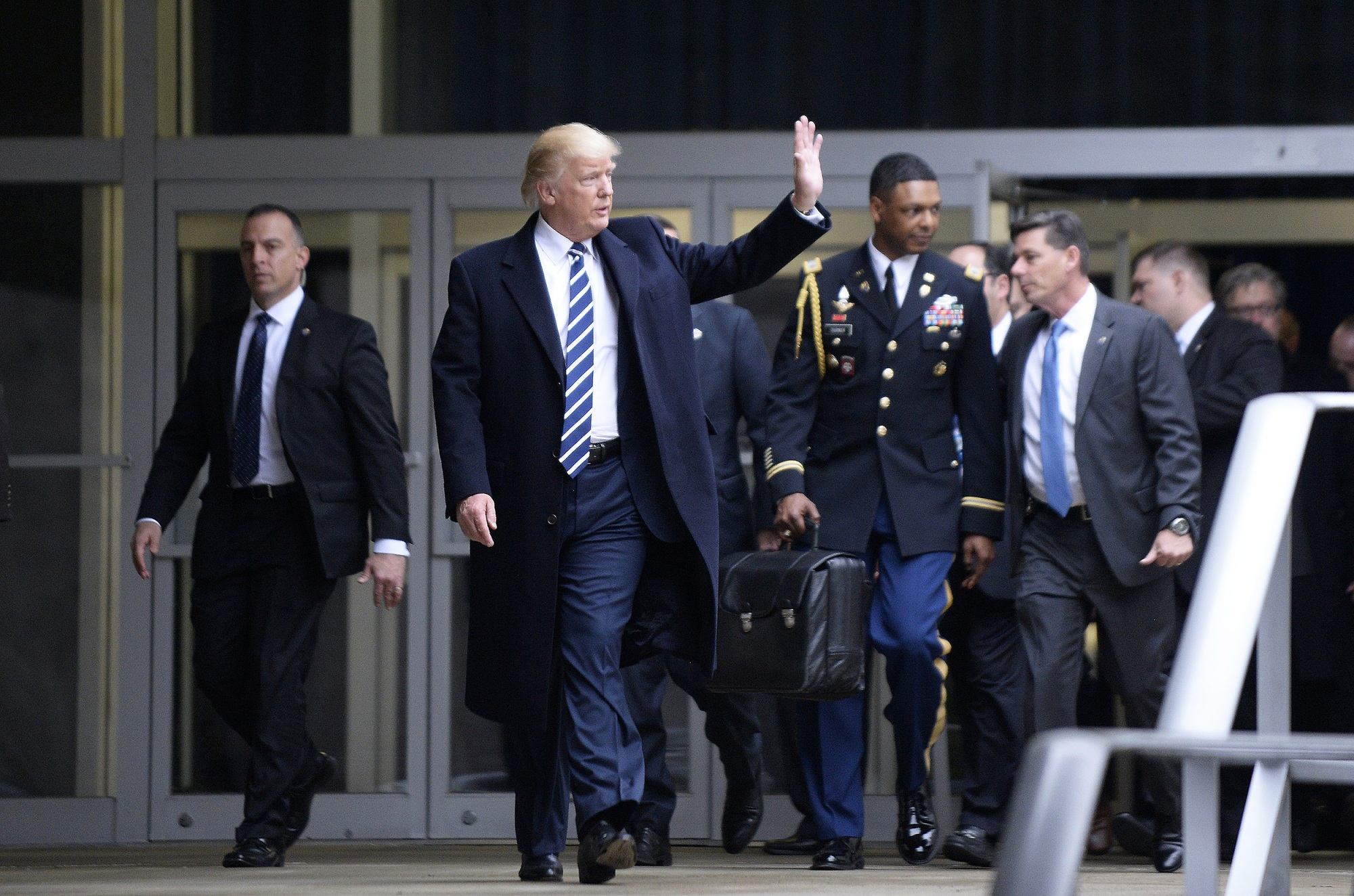 """TT Donald Trump rời trụ sở CIA ở Langley, Va., vào ngày 21 tháng 1 năm 2017. với một phụ tá quân sự mang """"quả bóng"""" hạt nhân .Olivier Doulier / Pool via Getty Images"""