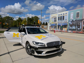 A self-driving car sits in front of a facade of storefronts in Mcity, the University of Michigan's testing facility for autonomous vehicles.