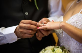 Image: A couple exchanges rings at a ceremony in Newark