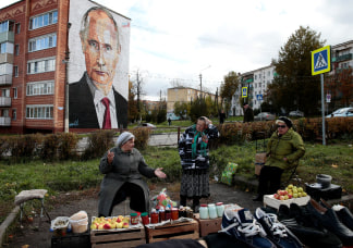 Image: Elderly women wait for customers as they sell their self-made food products at a street market, with a graffiti depicting Russian President Vladimir Putin on the wall of a house seen in the background, in the town of Kashira, outside Moscow