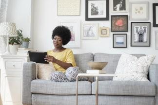 Image: African American woman using digital tablet on sofa