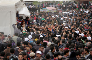 Image: Palestinians gather to receive lunch packages during a protest