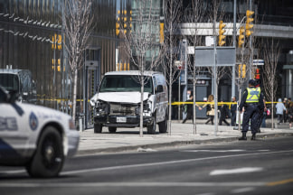 Image: Toronto police officers stand near a damaged van