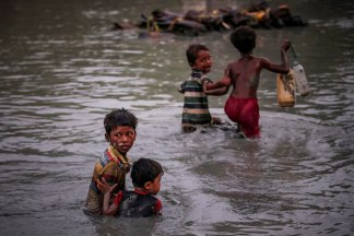 Image: Rohingya siblings fleeing violence hold one another as they cross the Naf River