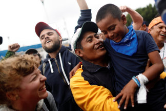 Image: A man and his son, members of a caravan of migrants from Central America, react near the San Ysidro checkpoint in Tijuana