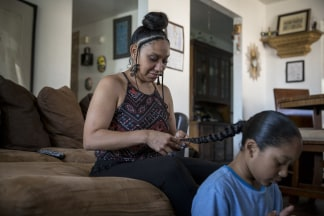 Image: Jaymie Rivera-Clemente, 37, braids her 10 year-old son RaDyn's hair at their home in Austin, Texas, May 9, 2018.