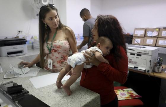 Image: Arelys Pulido, right, holds her two-month-old daughter Zuleidys Antonella Primera as they are processed for her baby's birth certificate at the Erazmo Meoz hospital in Cucuta