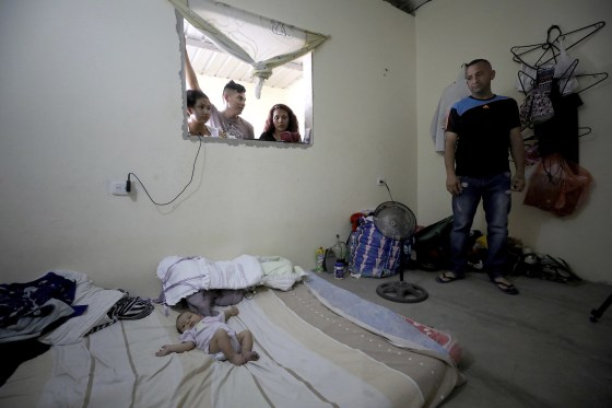 Image: Venezuelan migrat Jose Antonio Pulido stands next to her two-month-old daughter Zuleidys Antonella Primera at their home in Cucuta