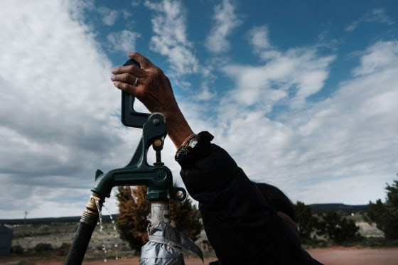 A member of the Navajo Nation fills bottles of water at a public tap in Thoreau, N.M., on June 5, 2019.