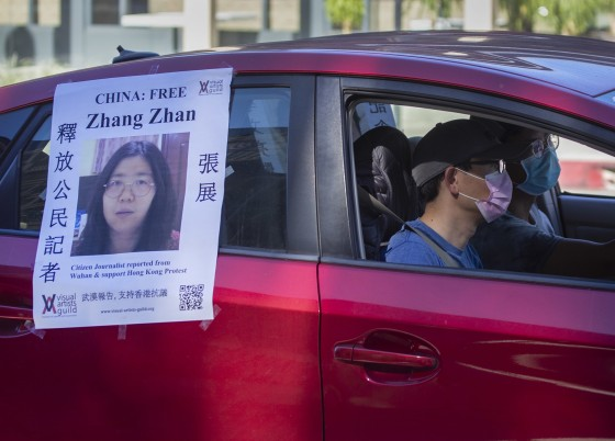 Image: A car follows a funeral caravan with poster of Zhang Zhan, a Chinese citizen journalist who criticized the Chinese government's handling of the coronavirus crisis and is being held in a Shanghai prison.