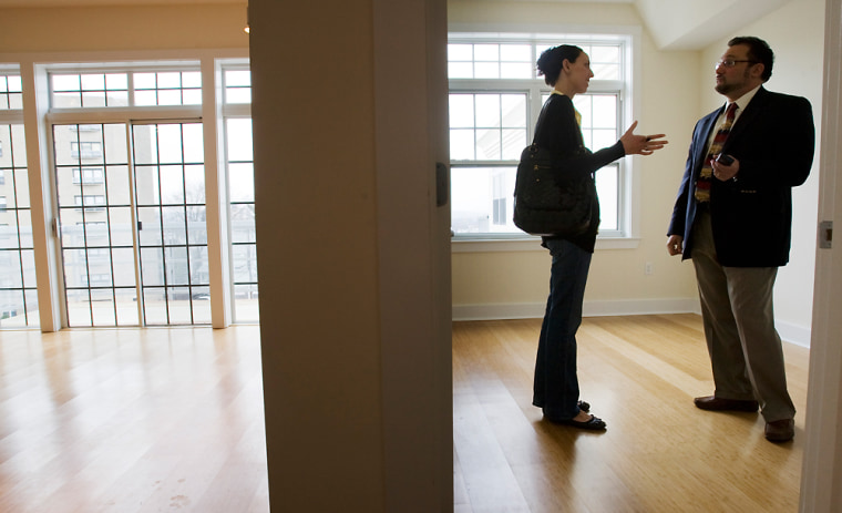 Image: Prospective home buyer Jessica Doctoroff talks to her real estate agent Stephen Bremis (R) while viewing a condominium for sale in Somerville, Mass.