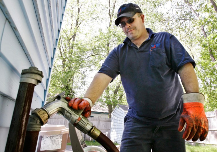 Tim Weeks makes a home heating oil delivery May 29, 2008, in Portland, Maine. Thousands of people locked into heating oil contracts as the price of crude soared over the summer, then watched prices descend below $50.