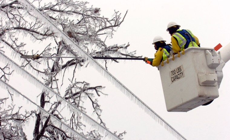 A line crew saws off limbs hanging across power lines in Fayetteville, Ark., on Thursday. More than 350,000 homes and businesses in the state were without power.