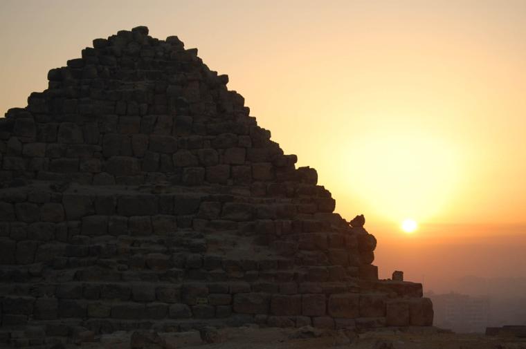 The sun rises above a pyramid at Giza, Egypt.