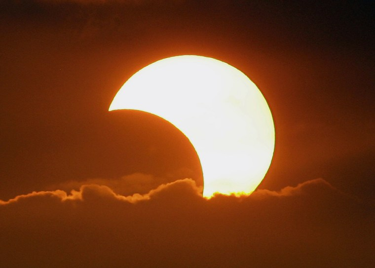 The moon casts a shadow at the sun blocking it partially in a partial solar eclipse