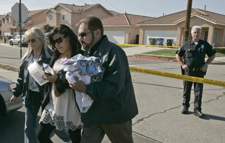A member of the Los Angeles Police Department's Crisis Response Team, left, helps evacuate a family living next to the home of a man, who apparently shot and killed his wife and five young children before committing suicide at their home in Wilmington, Calif. on Tuesday.