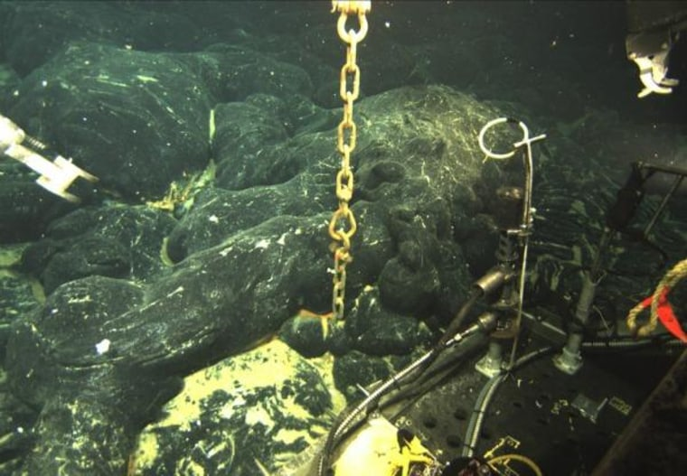 The chain is all that is visible of an ocean-bottom hydrophone, an instrument that detects earthquakes, buried in about 6 feet of new lava produced by a recent eruption at the Axial Seamount.