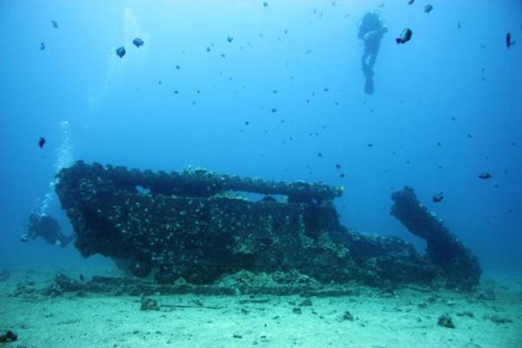 Divers inspect an amphibious LVT-4 (Landing Vehicle Tracked)from World War II.