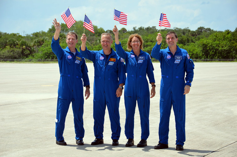 NASA's final space shuttle crew waves American flags celebrating their Fourth of July arrival at Kennedy Space Center for their launch scheduled for Friday. From left to right: commander Chris Ferguson, pilot Doug Hurley and mission specialists Sandy Magnus and Rex Walheim.