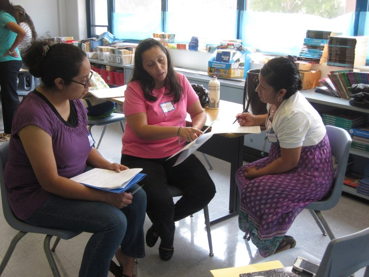Parent mentor coordinators with the Logan Square program prepare for a group presentation during a summer training session.