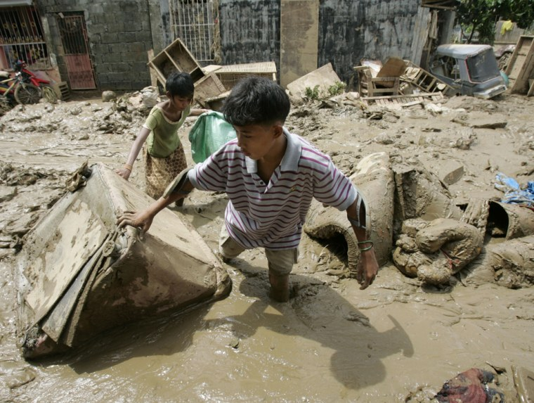 Image: Residents negotiate knee-deep mud at a remote village in Rodriguez, Rizal province, Philippines