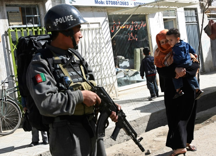 Image: An Afghan policeman stands guard at the site of an incident in Kabul