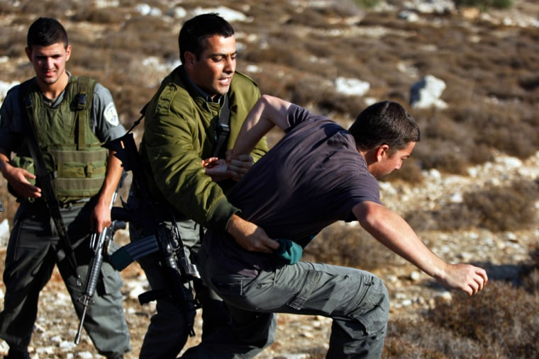 Israeli border police officers scuffle with a Jewish settler during an attempt to arrest him Monday next to the outpost of Migron, near the West Bank city of Ramallah.