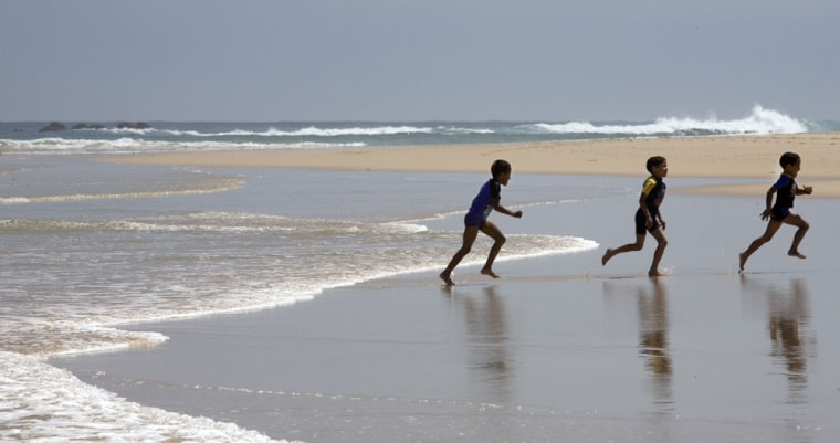 Three youngsters try to outrun an Indian ocean wave while playing on Sardinia Beach near Port Elizabeth, South Africa.