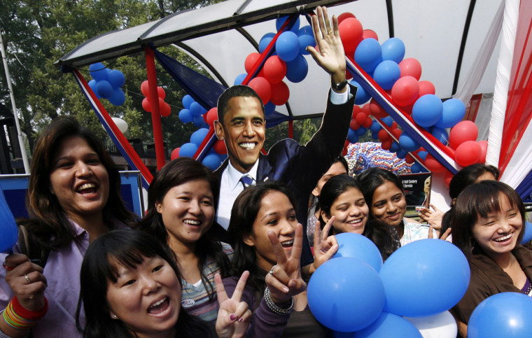 Image: College students cheer while posing with cutout of U.S. President-elect Senator Obama in New Delhi